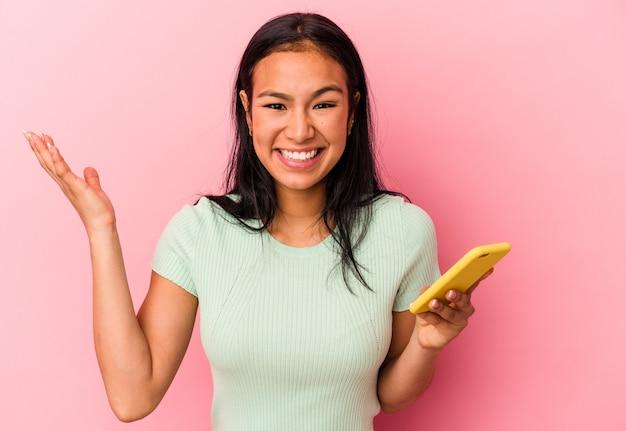 ピンクの背景に分離された携帯電話を持っている若いベネズエラの女性は、嬉しい驚きを受け取り、興奮し、手を上げます。