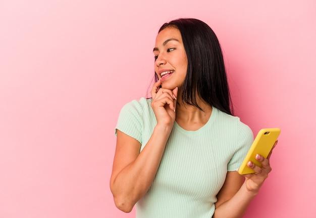 ピンクの背景に分離された携帯電話を持っている若いベネズエラの女性は、コピースペースを見ている何かについて考えてリラックスしました。
