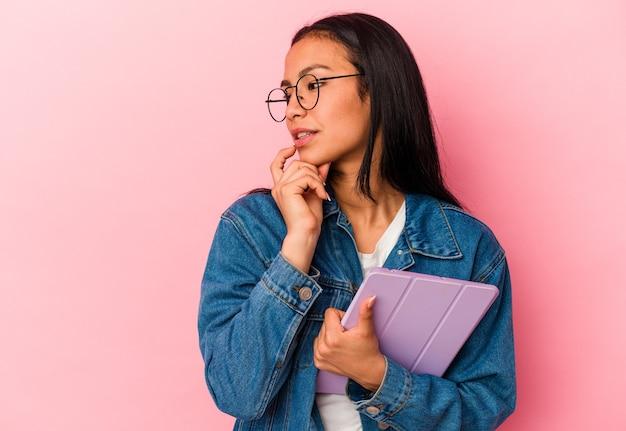 ピンクの背景に分離されたタブレットを保持している若いベネズエラの女性は、コピースペースを見ている何かについて考えてリラックスしました。