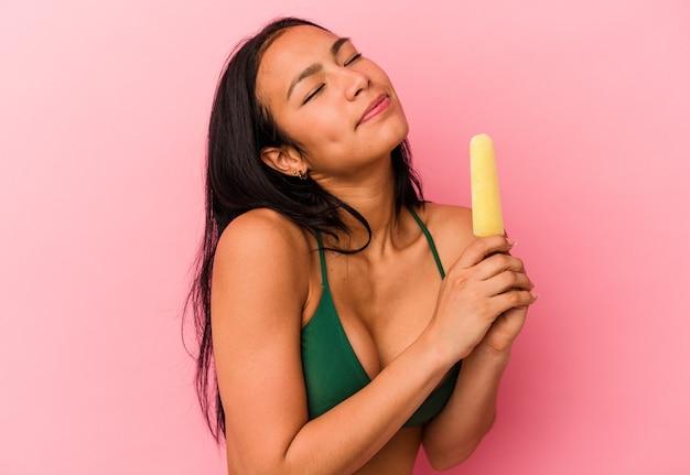 Молодая венесуэльская женщина, держащая мороженое на розовом фоне