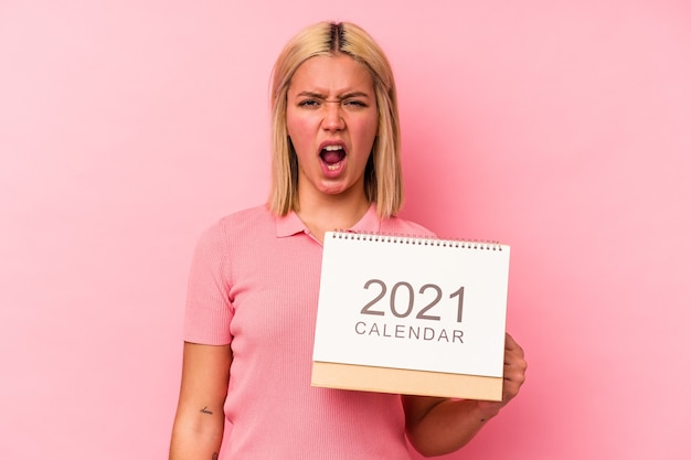 Young venezuelan woman holding a calendar isolated on pink background screaming very angry and aggressive.