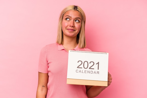 Young venezuelan woman holding a calendar isolated on pink wall dreaming of achieving goals and purposes