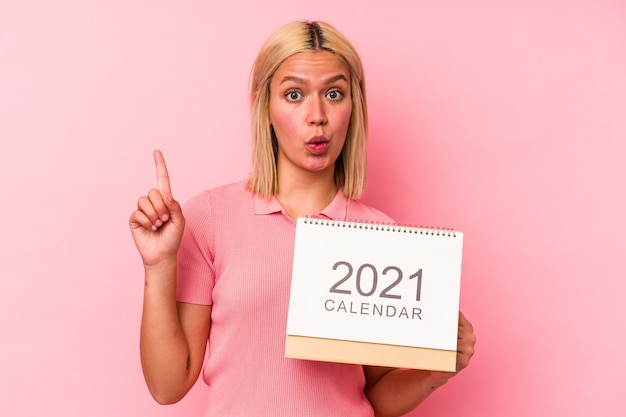 Young venezuelan woman holding a calendar isolated on pink wall having some great idea