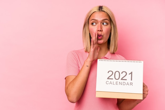 Young venezuelan woman holding a calendar isolated on pink wall is saying a secret hot braking news and looking aside