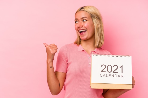 Young venezuelan woman holding a calendar isolated on pink wall points with thumb finger away, laughing and carefree.