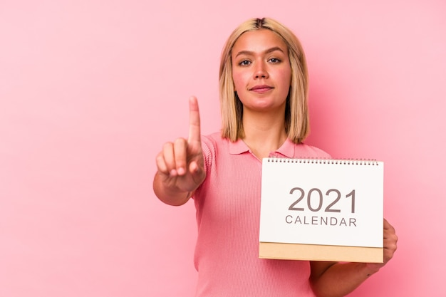 Young venezuelan woman holding a calendar isolated on pink wall showing number one with finger