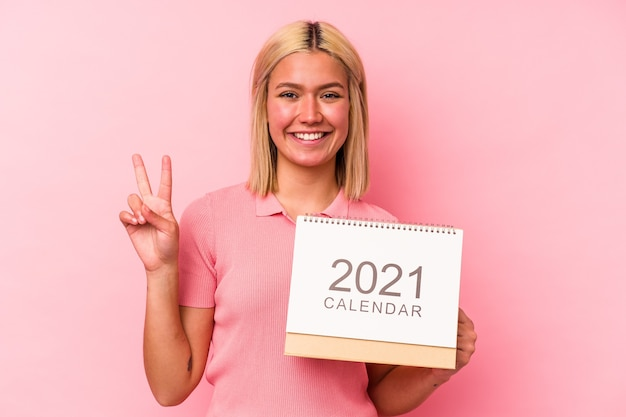 Young venezuelan woman holding a calendar isolated on pink wall showing number two with fingers.