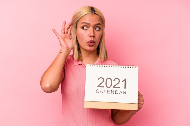 Young venezuelan woman holding a calendar isolated on pink wall trying to listening a gossip