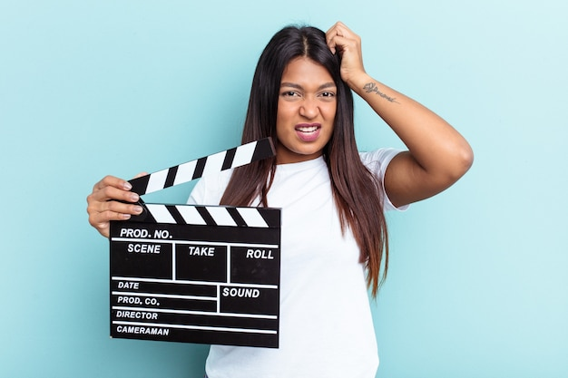 Young venezuelan woman holding a clapperboard isolated on blue background being shocked, she has remembered important meeting.