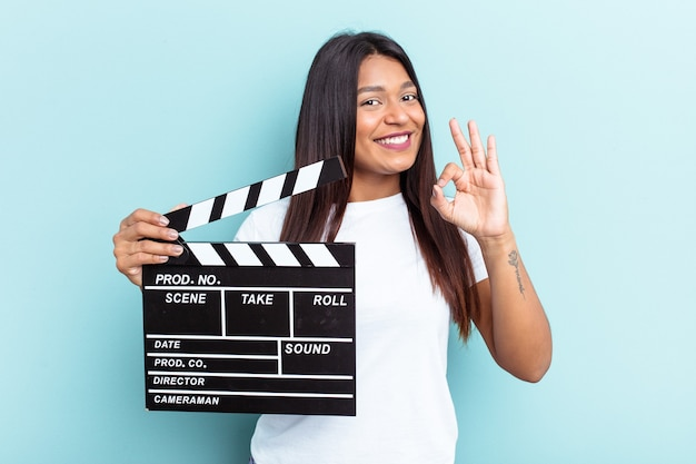 Young venezuelan woman holding a clapperboard isolated on blue background cheerful and confident showing ok gesture.