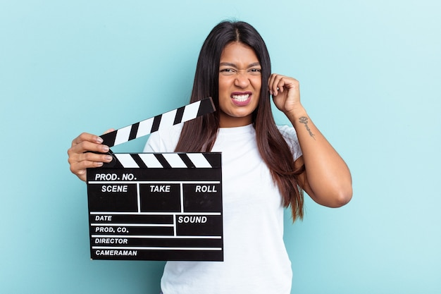 Young venezuelan woman holding a clapperboard isolated on blue background covering ears with hands.