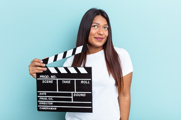 Young venezuelan woman holding a clapperboard isolated on blue background dreaming of achieving goals and purposes