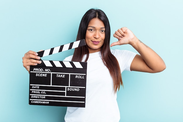 Young venezuelan woman holding a clapperboard isolated on blue background feels proud and self confident, example to follow.