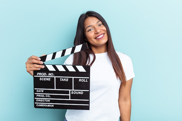 Young venezuelan woman holding a clapperboard isolated on blue background happy, smiling and cheerful.