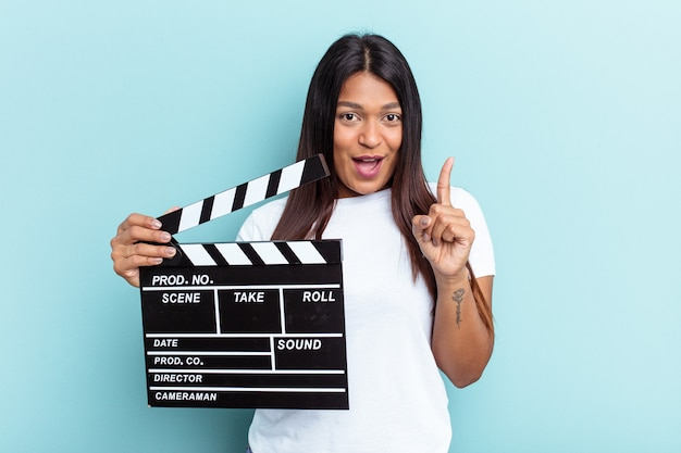 Young venezuelan woman holding a clapperboard isolated on blue background having an idea, inspiration concept.