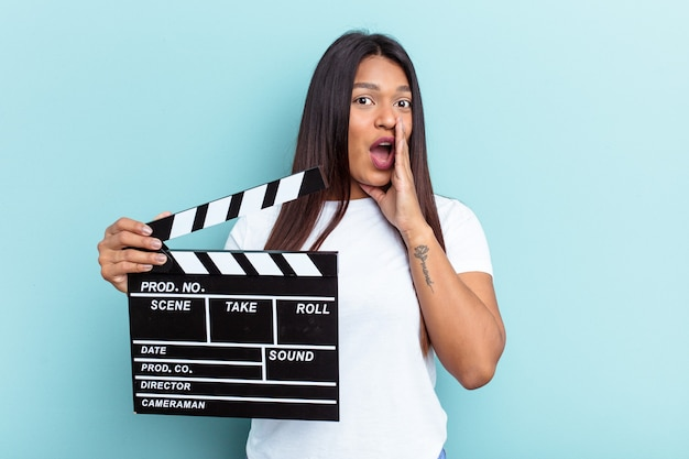Young venezuelan woman holding a clapperboard isolated on blue background is saying a secret hot braking news and looking aside