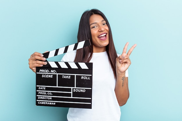 Young venezuelan woman holding a clapperboard isolated on blue background joyful and carefree showing a peace symbol with fingers.