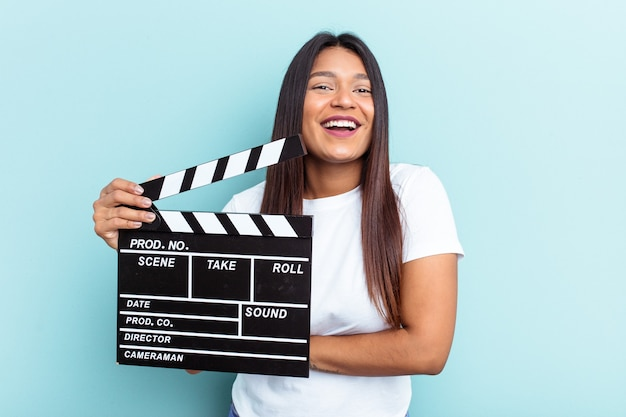 Young venezuelan woman holding a clapperboard isolated on blue background laughing and having fun.