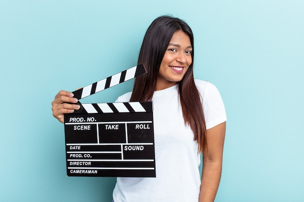 Young venezuelan woman holding a clapperboard isolated on blue background looks aside smiling, cheerful and pleasant.