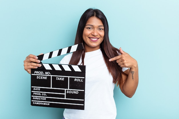 Young venezuelan woman holding a clapperboard isolated on blue background person pointing by hand to a shirt copy space, proud and confident