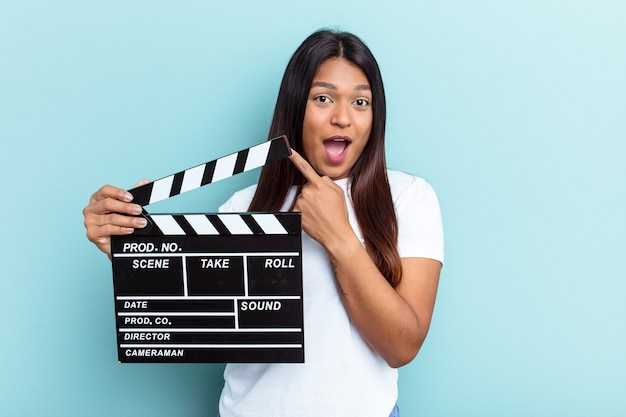 Young venezuelan woman holding a clapperboard isolated on blue background pointing to the side