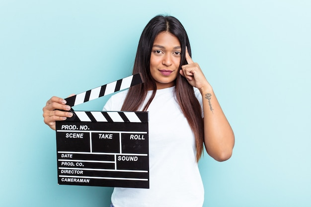 Young venezuelan woman holding a clapperboard isolated on blue background pointing temple with finger, thinking, focused on a task.