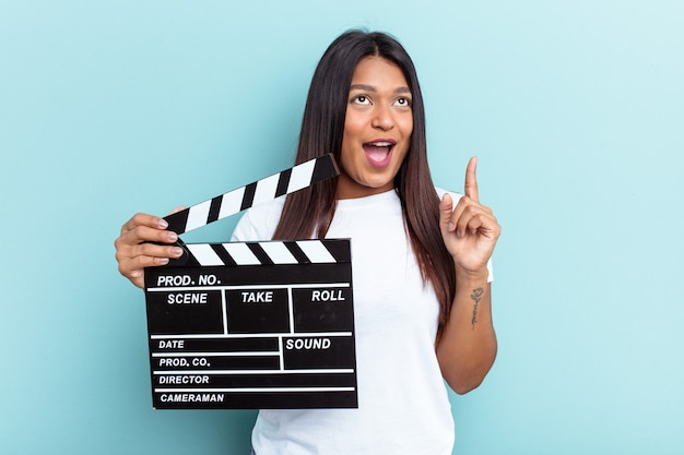 Young venezuelan woman holding a clapperboard isolated on blue background pointing upside with opened mouth.