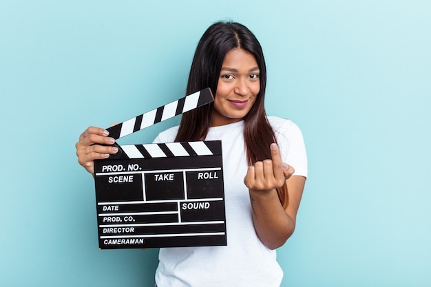 Young venezuelan woman holding a clapperboard isolated on blue background pointing with finger at you as if inviting come closer.