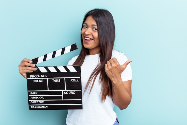Young venezuelan woman holding a clapperboard isolated on blue background points with thumb finger away, laughing and carefree.