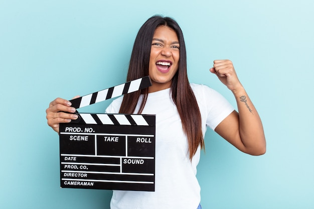 Young venezuelan woman holding a clapperboard isolated on blue background raising fist after a victory, winner concept.