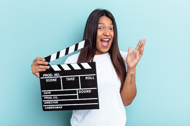 Young venezuelan woman holding a clapperboard isolated on blue background receiving a pleasant surprise, excited and raising hands.