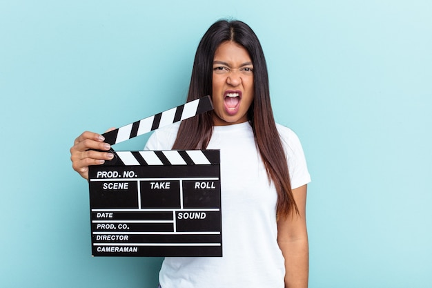 Young venezuelan woman holding a clapperboard isolated on blue background screaming very angry and aggressive.