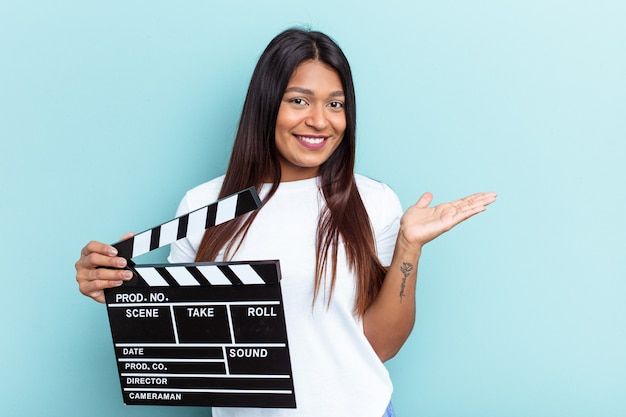 Young venezuelan woman holding a clapperboard isolated on blue background showing a copy space on a palm and holding another hand on waist.