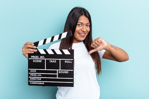 Young venezuelan woman holding a clapperboard isolated on blue background showing a dislike gesture, thumbs down. disagreement concept.