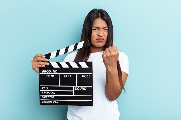 Young venezuelan woman holding a clapperboard isolated on blue background showing fist to camera, aggressive facial expression.