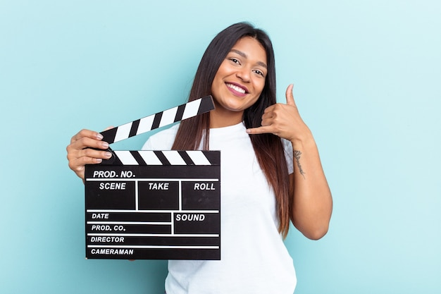 Young venezuelan woman holding a clapperboard isolated on blue background showing a mobile phone call gesture with fingers.