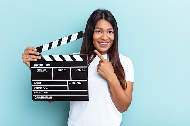 Young venezuelan woman holding a clapperboard isolated on blue background smiling and pointing aside, showing something at blank space.