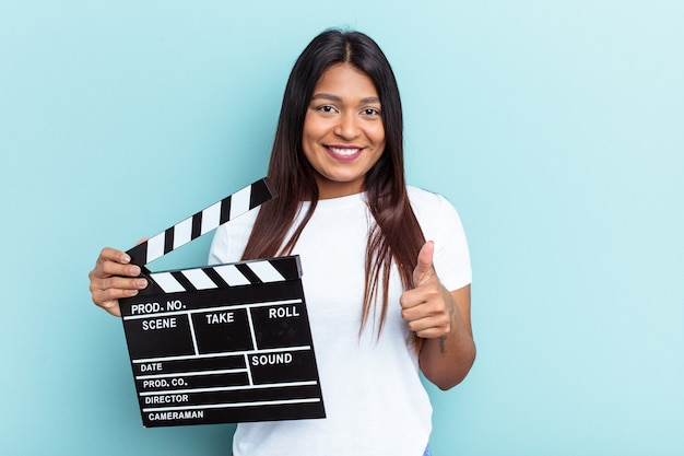 Young venezuelan woman holding a clapperboard isolated on blue background smiling and raising thumb up