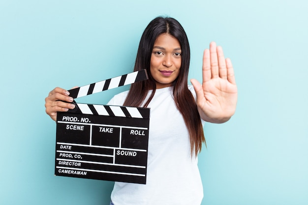 Young venezuelan woman holding a clapperboard isolated on blue background standing with outstretched hand showing stop sign, preventing you.