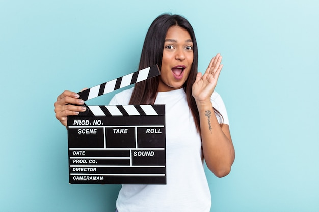 Young venezuelan woman holding a clapperboard isolated on blue background surprised and shocked.