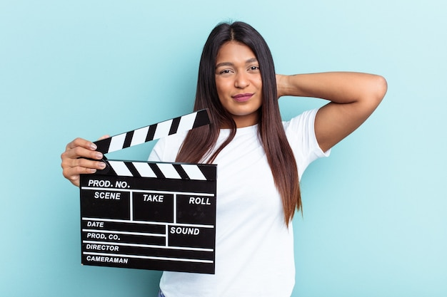 Young venezuelan woman holding a clapperboard isolated on blue background touching back of head, thinking and making a choice.