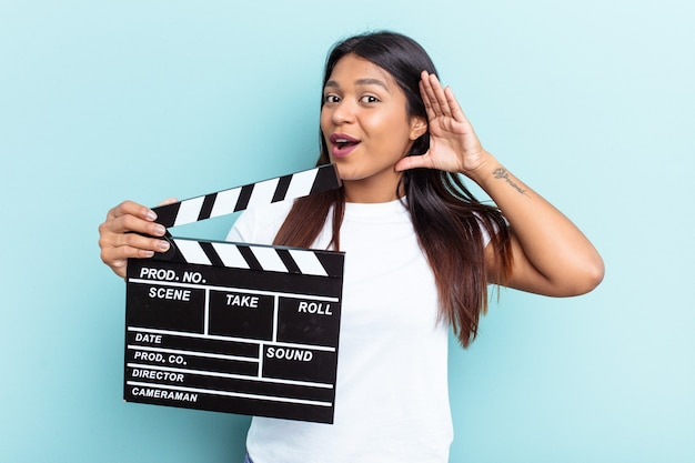 Young venezuelan woman holding a clapperboard isolated on blue background trying to listening a gossip.