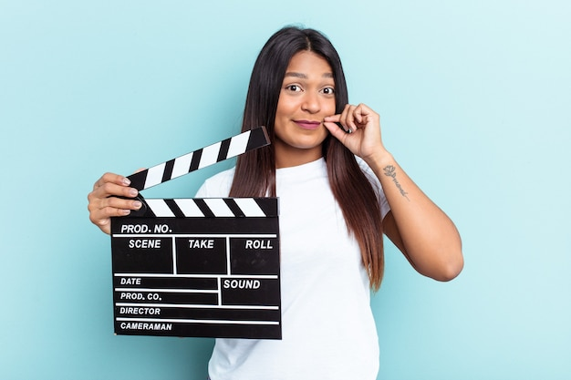 Young venezuelan woman holding a clapperboard isolated on blue background with fingers on lips keeping a secret.