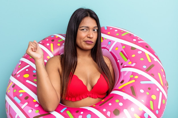Young venezuelan woman holding donut inflatable isolated on blue background confused, feels doubtful and unsure.