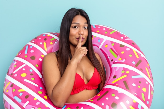 Young venezuelan woman holding donut inflatable isolated on blue background keeping a secret or asking for silence.