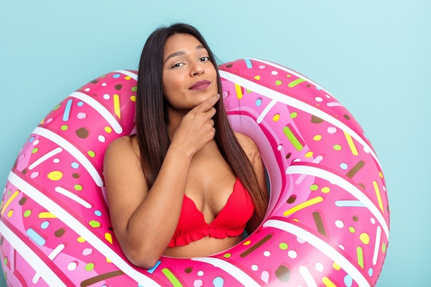 Young venezuelan woman holding donut inflatable isolated on blue background looking sideways with doubtful and skeptical expression.