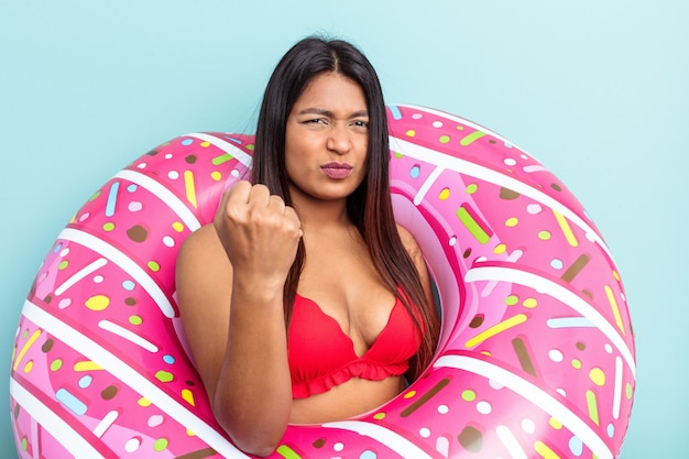 Young venezuelan woman holding donut inflatable isolated on blue background showing fist to camera, aggressive facial expression.
