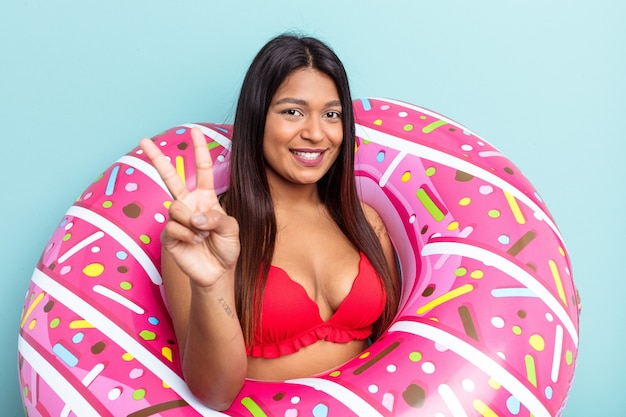 Young venezuelan woman holding donut inflatable isolated on blue background showing number two with fingers.