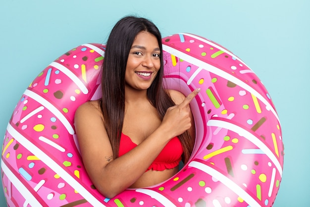 Young venezuelan woman holding donut inflatable isolated on blue background smiling and pointing aside, showing something at blank space.