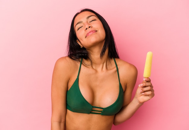 Young venezuelan woman holding an ice cream isolated on pink background dreaming of achieving goals and purposes
